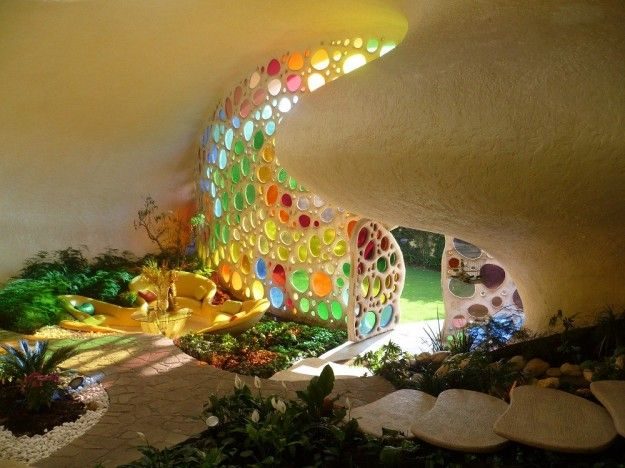 Organically shaped entrance of an Eartship home, with colored glass wall inserts