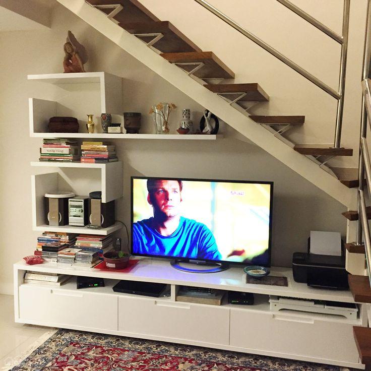 Apartamento duplex com escada em degrau de madeira e guarda-corpo em aço inox. O espaço abaixo dela foi usado como rack de TV e estante para guardar livros e outros objetos, aproveitando e seguindo o desenho da escada. Projeto de AG. arquitetura.