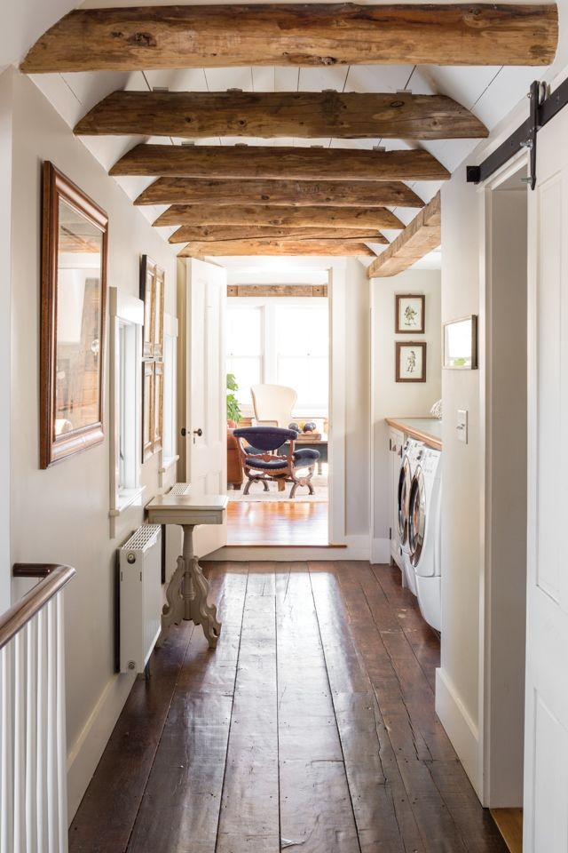 Spang Builders reused materials throughout the home, such as these wooden ceiling beams (opposite) in the laundry area.