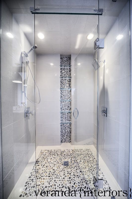 Pebble floor and back-splash, modern tile, frame-less glass door and panels, narrow dual shower.