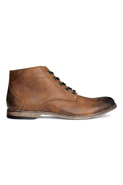 Высокие ботинки: Пара высоких ботинок из искусственной кожи со шнуровкой спереди. Резиновая подошва.