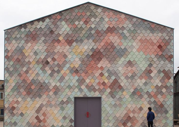 Handmade concrete tiles give a scaly facade to this collaborative workplace building designed for artists and designers in east London.