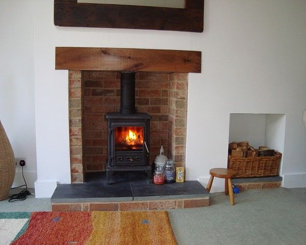 Wood burner with wood mantle, brick surround and tile base.