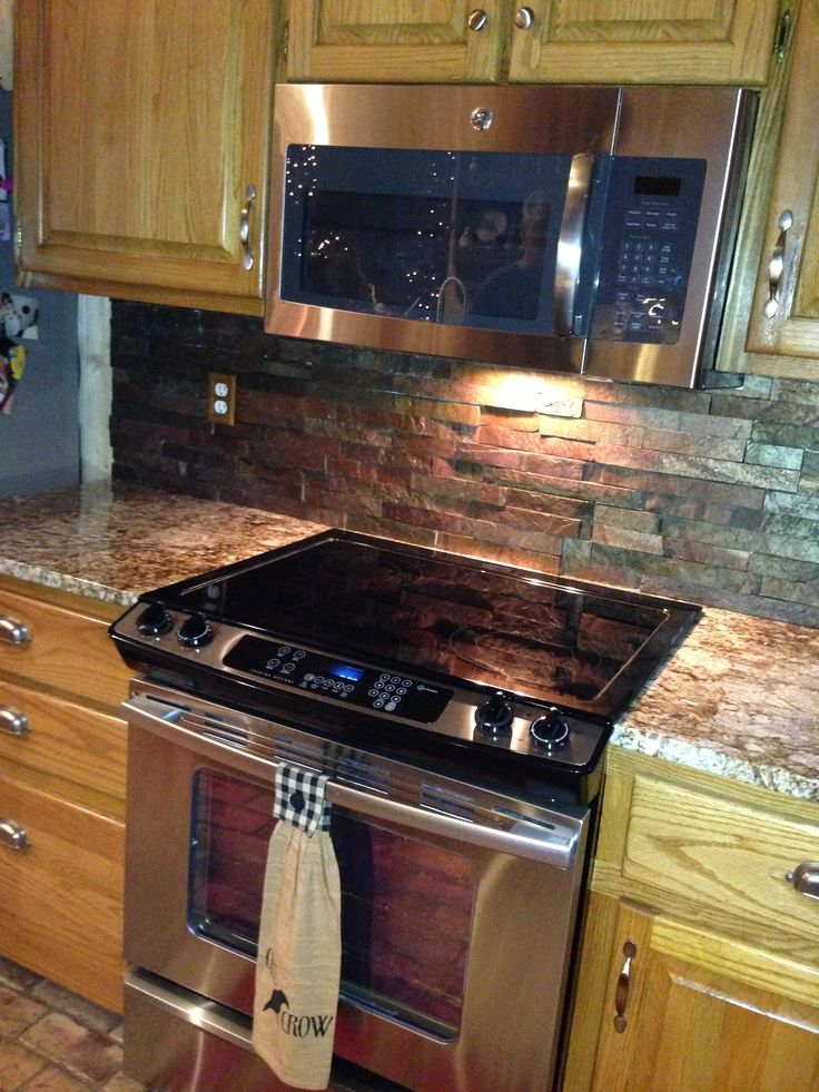 Love the backless stove, with micro above, rustic backsplash.