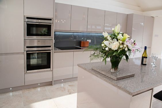 Gloss Cashmere Handleless with Samsung 'Saltoro Cliff' Quartz worktop. Feature radiator by Bisque. Splash back is Lustrolite 'Titan' with a Blanco Silgranite sink in the 'Alumetallic' finish, taps are Grohe Duo Red. Neff single oven, Combi Oven and warming drawer, Neff Four Zone Induction Hob, Neff Dishwasher, CDA Tall Larder Fridge and Freezer, CDA 30cm Wine Cooler,... Read More