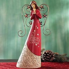 Christmas Angels | Red Angel Figurine - A Personal Creations Exclusive! An inspirational holiday accent, our joyful angel bows her head in prayer. The stars on her red gown and gold wings are a beautiful reminder of the very first Christmas.