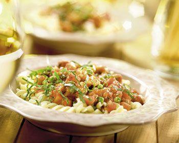 Pel en snipper de ui. Pers de knoflook uit, snijd de wortels in kleine blokjes en de basilicum in reepjes. Snijd de kipfilet in kleine blokjes.Verwarm de olijfolie in een wok of hapjespan en bak hierin het spek zachtjes uit. Schep de ui en knoflook erdoor en fruit ze zachtjes glazig. Bestrooi de blokjes kip met zout en peper en schep ze door het mengsel in de pan. Bak de blokjes kip rondom bruin.Schep de wortel, doperwten en Bertolli pastasaus kruidig erbij en smoor de saus in 10 - 15…