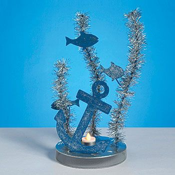 Our Under the Sea Centerpiece features a blue metal anchor with three metal fishes and silver garland seaweed accents. Each Under the Sea Centerpiece measures 15 1/2 inches high.
