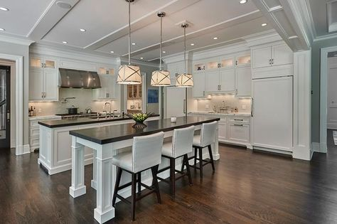 Stunning kitchen features two kitchen islands: one island topped with honed black marble lined with white leather nailhead counter stools illuminated by Grosvenor Single Pendants and the other island topped with honed black marble fitted with a sink and deck mount faucet.