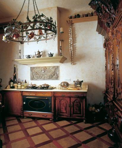 Stylizowane na stare komody szafki kuchenne przykryto kamiennym blatem. Gzyms komina jest z piaskowca.