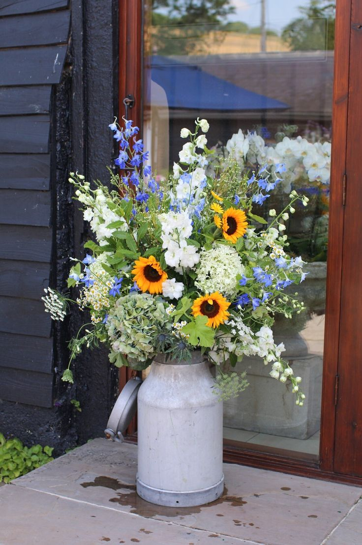 Milk churns filled with delphiniums, hydrangeas and sunflowers by Rose Cottage Flowers