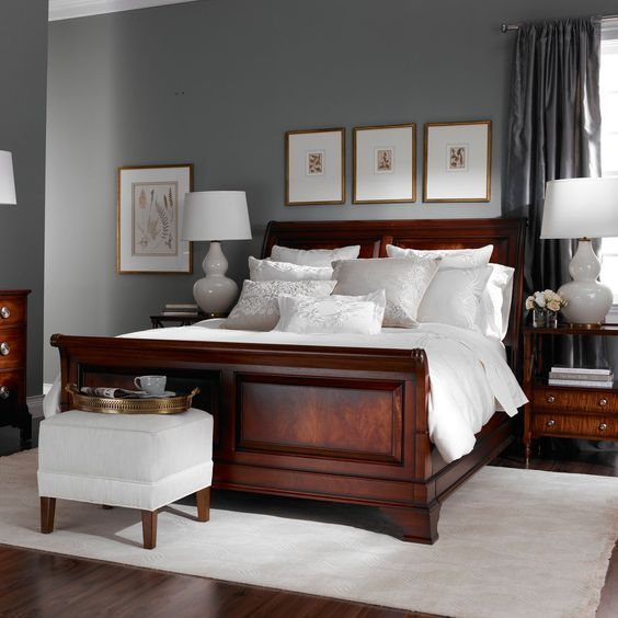 Grey walls and dark red wood tones coupled with gold frames and white crisp fabrics.