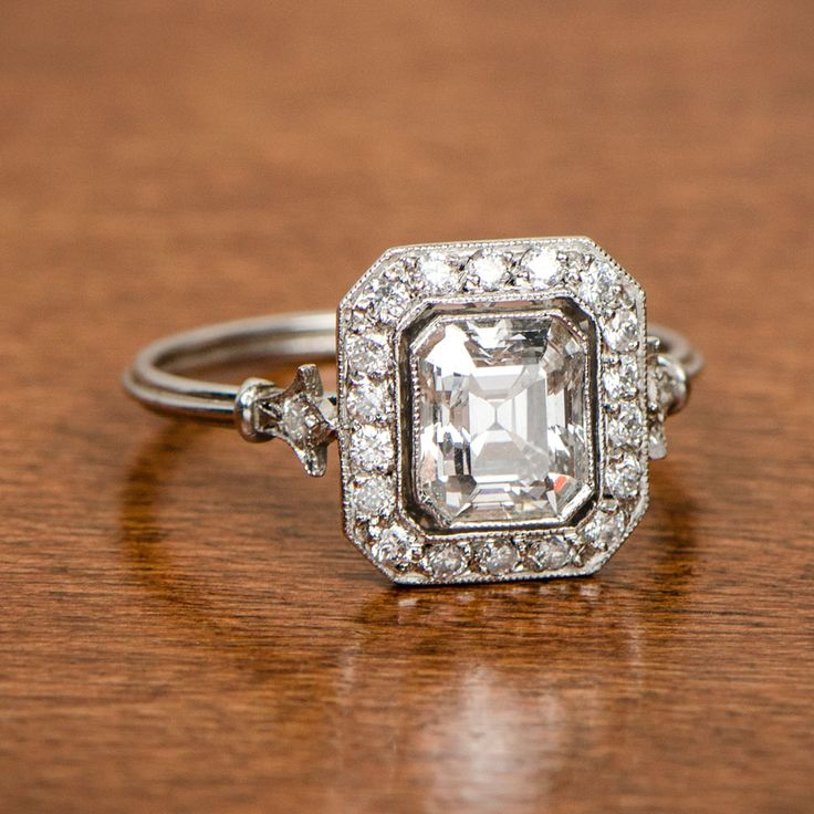 Antique emerald cut surrounded by a halo old mine diamonds.