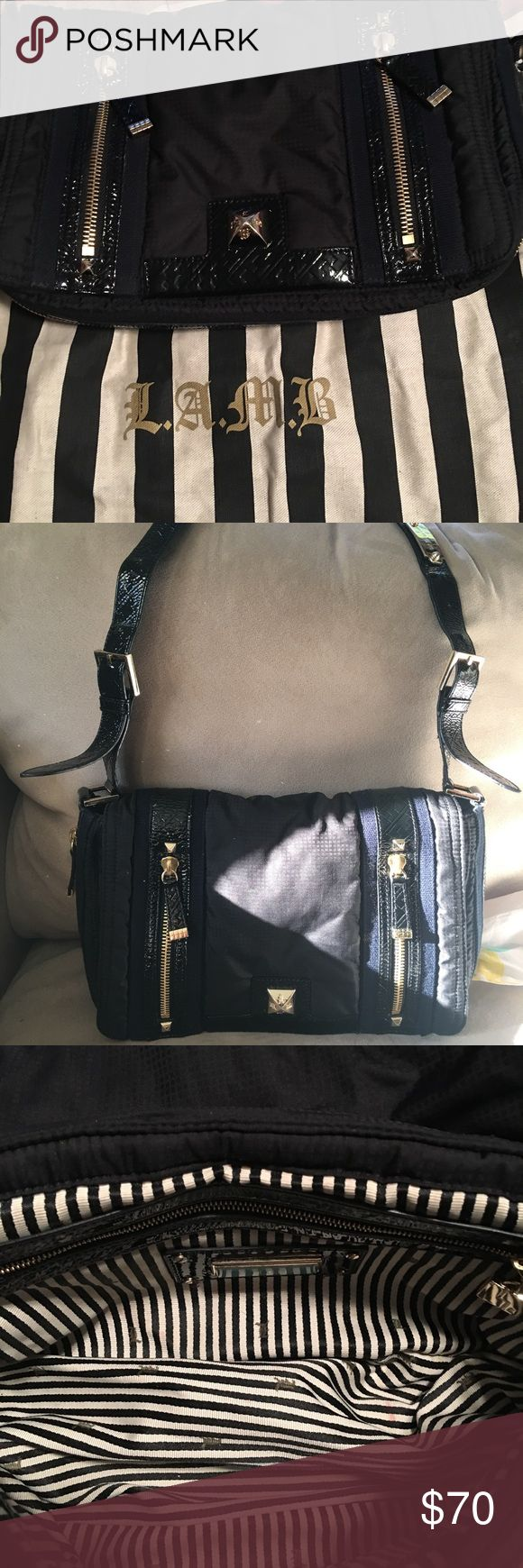 Very pretty over shoulder LAMB bag. Stylish authentic L.A.M.B. By Gwen Stephani bag.  Black with golden buckles and zippers. Adjustable shoulder strap. Signature black and white striped inside. Perfect condition. LAMB Bags Crossbody Bags