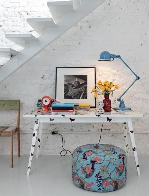 home office embaixo da escada, mesa co borboletas, luminária articulada azul, puff redondo estampado azul, parede de tijolos branca