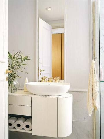 O espelho delimitado em frente à cuba sobreposta verticaliza o ambiente. Como a entrada do boxe fica à direita da pia, o arquiteto projetou um charmoso armário com extremidade arredondada para facilitar a passagem. Projeto de Ricardo Umada.