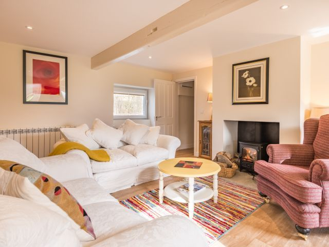 Our new pet friendly holiday cottage near Cockermouth is spacious and cosy. The sitting room features a wood burning stove and sumptuous sofas.