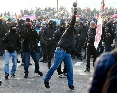 フランクフルトにある欧州中央銀行(ECB)の新本部前で18日、警官隊と衝突し石を投げるデモ参加者(ロイター=共同) ▼18Mar2015共同通信|欧州中銀で衝突、88人負傷 独西部、約1万人がデモ http://www.47news.jp/CN/201503/CN2015031801001870.html