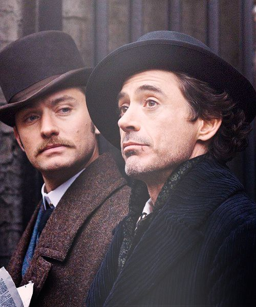 Robert Downey Jr. and Jude Law. Watson stares at Holmes in wonderment who is staring at something else in wonderment.