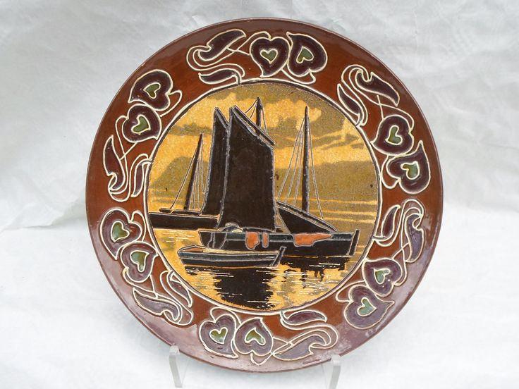 A late 19th / early 20th century Wileman Foley Faience wall plaque, designed by Frederick A Rhead, having a tonal seascape with boats and sails executed in sgraffito, the border decorated with art nouveau-style flowers, numbered verso 11049B with the Wileman stamp, 30cm diameter. Literature: Bernard Bumpus, 'Collecting Rhead Pottery' (Francis Joseph, 1999), Page 76, Plate 114