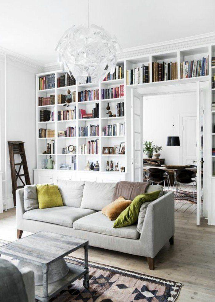 bibliotheque murale blanche et sofa gris avec coussins décoratifs