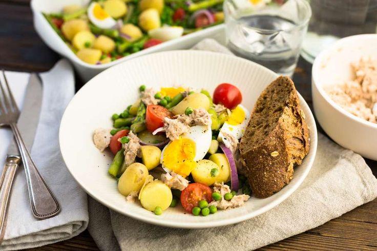 Recept voor frisse lentesalade voor 4 personen. Met zout, olijfolie, peper, groene asperge, tomaat, stokbrood, tuinerwten (diepvries), ei, krieltjes, rode ui, tonijn uit blik, mayonaise, yoghurt en citroensap