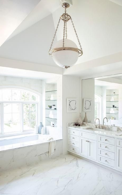 Chic bathroom features a Modern Globe Pendant illuminating a white dual washstand topped with gray and white marble under a full length mirror. Master bathroom boasts a marble clad tub placed under an alcove filled with glass shelves.