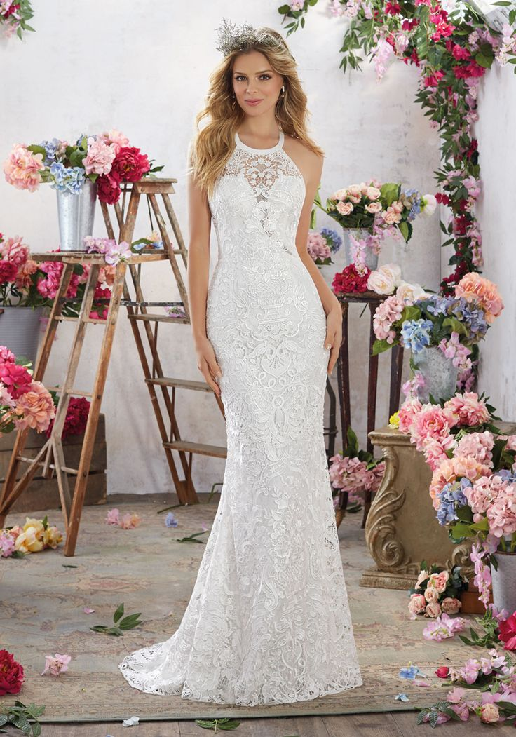 Cut-in shoulders frame the sheer lace jewel neckline atop the indented V-bodice of this Mori Lee Voyage 6851 Maybelle sleeveless Guipure lace wedding dress. This fitted gown features a double cutout back and finishes in a sweep train.