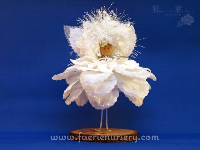 """Please meet Snowflake of the Northern Faerie Line.  Snowflake comes as a numbered edition - ordered by request only.  Snowflake stands just over 5"""" in height. She has a silver metallic wired body with a white heart shaped pony bead as a bodice. Her dress is made from 14 layers of silk flower ..."""