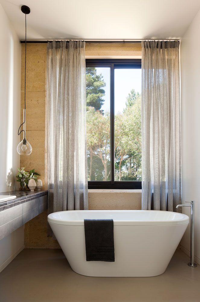 Lve rammed earth... Robson Rak Architects // Merricks House // freestanding bathtub; curtains; feature pendant light; rammed earth walls