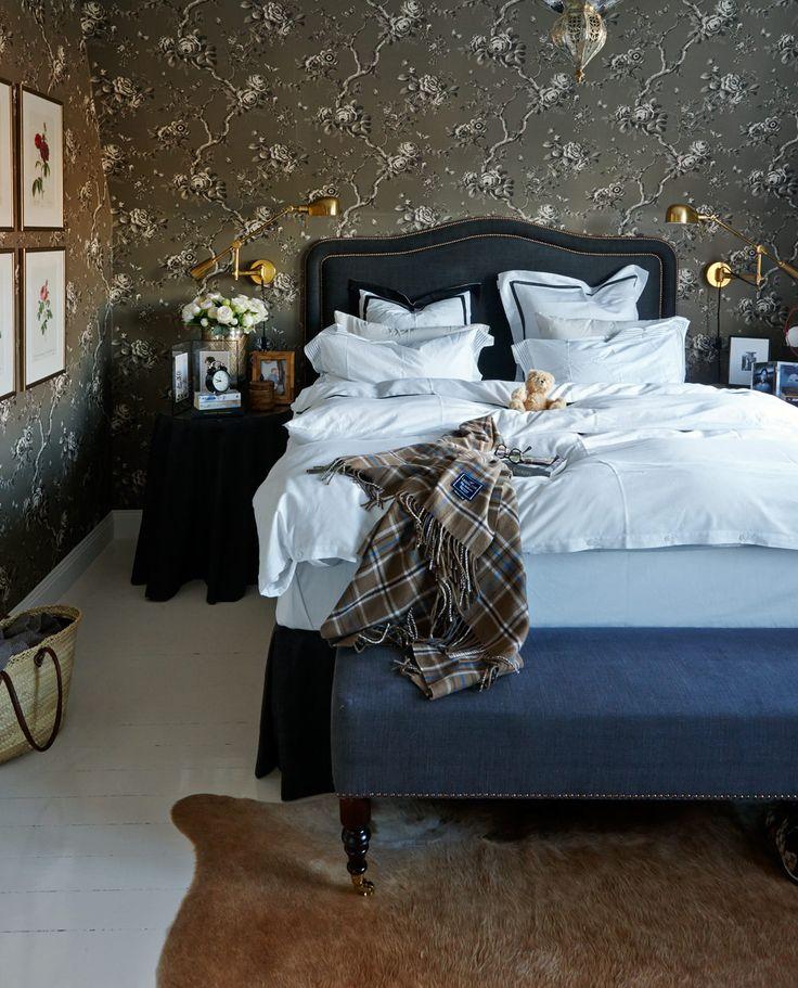 gray floral print wallpaper, brass sconces and upholstered headboard with nailhead trim (Leila Lindholm, Sköna hem)