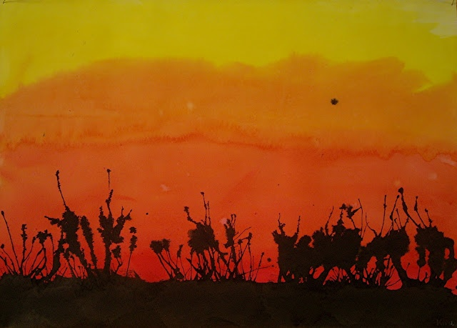 sunset painting with black outline done by blowing paint through straws