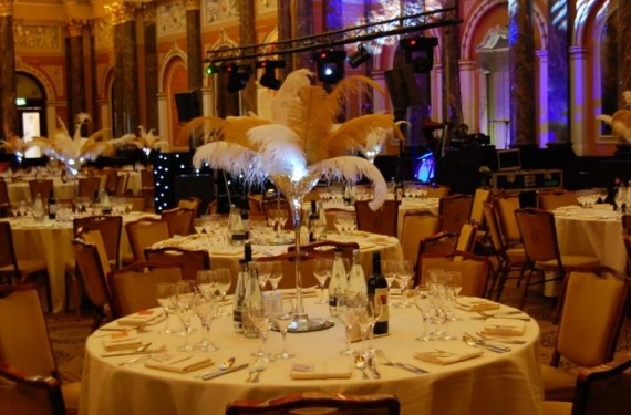 dramatic table centres which consisted on giant martini glasses with large ostrich feathers in golds and white and strings of pea lights