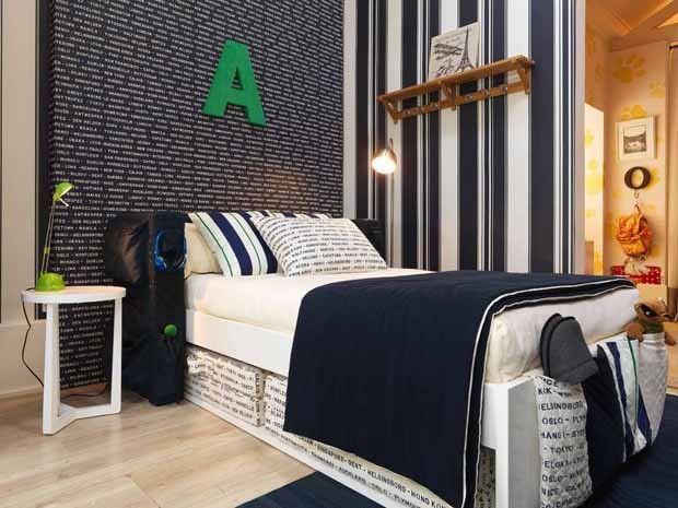 Quarto de menino adolescente com cama de solteiro, papel de parede com listras azul marinho e branco, roupa de cama azul marinho e branco