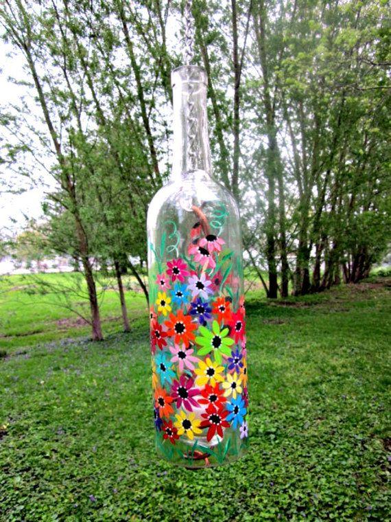 Bouteille de vin clair recyclé dans une belle suspension lampe de jardin, patio lumière, lampe-tempête. Peint à la main avec des fleurs colorées tout autour.  Fil de cuivre torsadé dans un tourbillon est titulaire dun porte-bougie votive et est de joindre à une chaîne. Le fond de la bouteille a été coupé et poncé.  Soulever la bouteille par la lumière (get est un peu chaud autour de la bouteille avec une vraie bougie brûler) de tour de cou de votre bougie ou utiliser une bougie led…