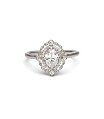 Inspired by the delicate details found in vintage designs, this stunning engagement ring juxtaposes touches of modern simplicity and antique charm to create a piece that is nothing short of perfection! Set in a cool platinum, this ring features a center 0.53ct oval diamond, and two glimmering diamond halos surrounding the center stone. Lacy and feminine, yet substantial and decadant, this one-of-a-kind ring is the perfect blend of vintage chic! Size 6 | (310) 310-3998