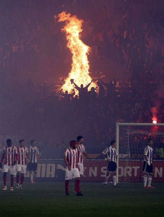 Unruly fans light a bonfire in the stands of a chaotic derby match between Red Star and Partizan in Belgrade
