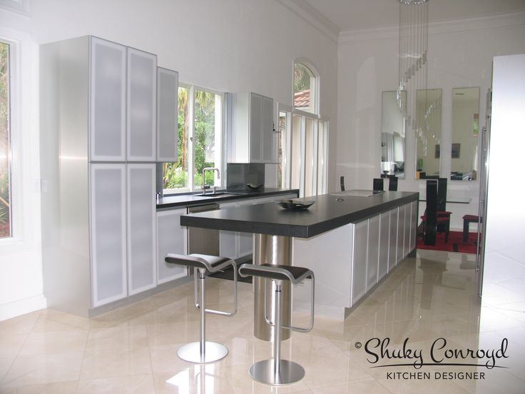 Contemporary kitchen design by Shuky Conroyd, Kitchen and Bath Designer. Aluminum doors with frosted glass give this kitchen a transparent feel. Hi tech but yet soft. A full kitchen remodel project including opening all walls and adding a big island.