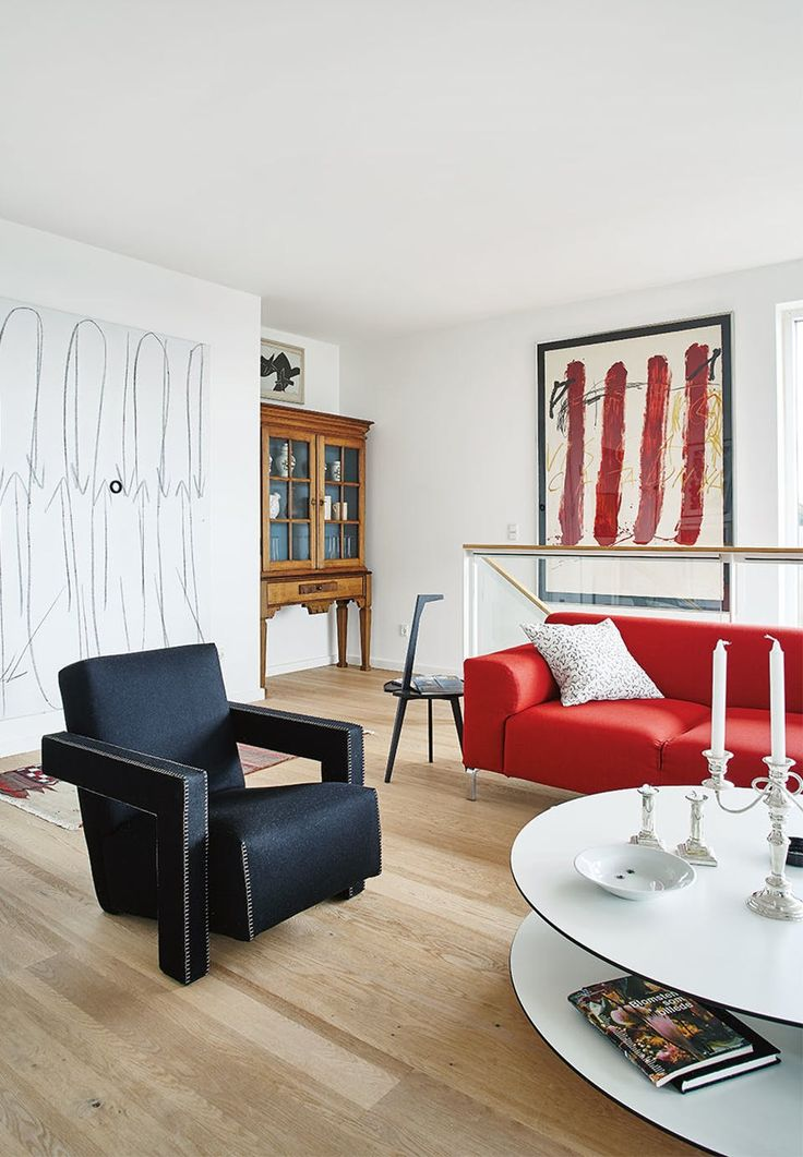 Living room dominated by the red sofa, Greg, from Zanotta. In front a coffee table, Giro2 from Zanotta, and a distinct sculptural black armchair, designed by Rietveld, Cassina.