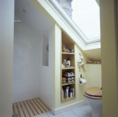 Small attic bath with use of storage in otherwise unusable area