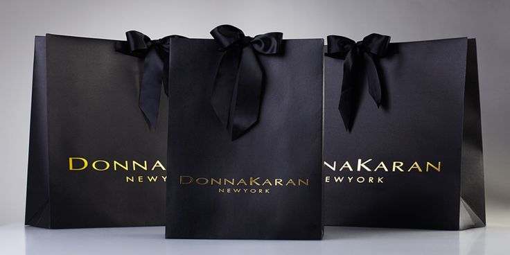 Donna Karan Handmade black dyed paper shopping bags with embossed gold foil stamped logo and black satin ribbon-tie detail.