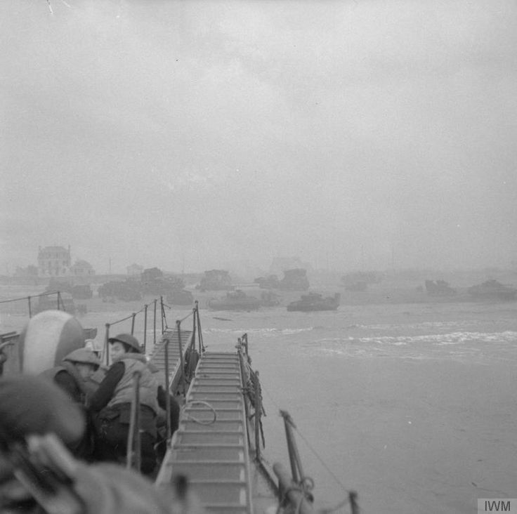 Commandos approach Sword Beach in a Landing Craft Infantry (LCI). Ahead, the beach is crowded with tanks and vehicles of 27th Armoured Brigade and 79th Armoured Division.