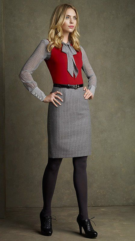A red vest with grey blouse and skirt, perfect pop of color
