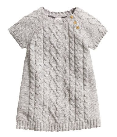 Short-sleeved knit dress in a cotton blend with wool content. Knit pattern at front and on sleeves. Buttons on one shoulder.