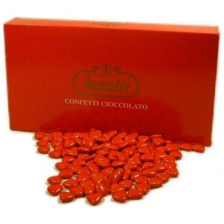 un cuore di ciccolato con la carta rossa e i confetti rossi a cuore ...