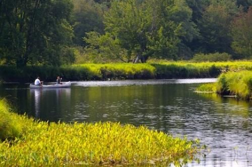 Photo of a couple canoeing on the scenic Mersey River in Kejimkujik National Park and National Historic Site in Nova Scotia.