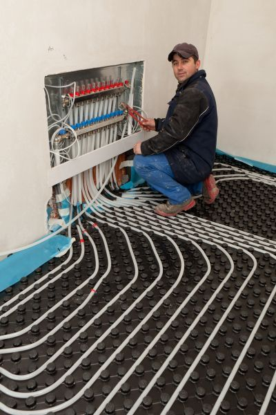 In a hydronic radiant-floor heating system, PEX tubing carries the fluid heated by the boiler from the manifold in the wall to the various heating zones. In this case, a lightweight concrete slab will be poured over the installed tubing.