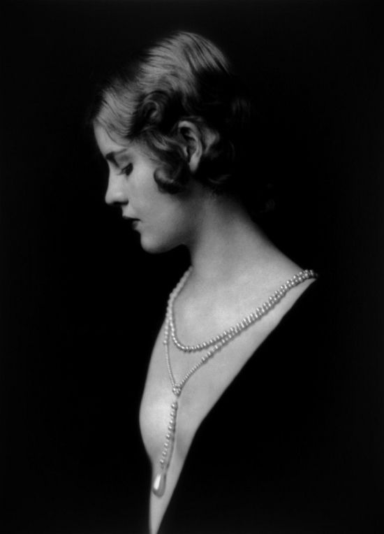 Portrait of Ziegfeld Follies girl Caja Eric wearing a low cut dress with long pearl drop necklace, 1920s