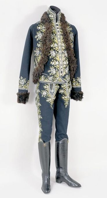"Gentleman's suit, 1770-1780, Hungary, budge, felt, embroidered with flat stitch, braiding. ""...made of dark blue felt...set-in sleeves; the borders are embroidered with alternating motifs of big and small bunches of flowers, in green and white silk thread. Lined with brown lamb's fur ( a later addition)...width adjustable with a lace at the back. The borders and the standing collar are embroidered with the motifs described above. Decorated with white and green silk braids all around."""