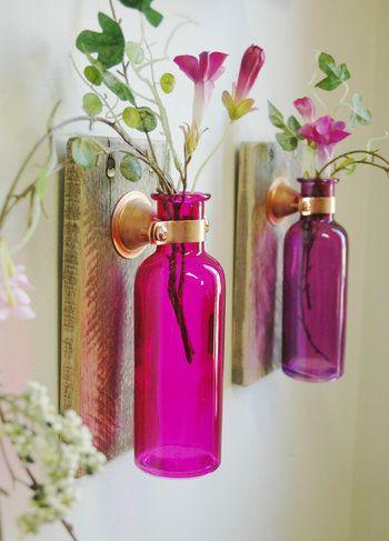 鮮やかな花瓶で気分も明るくなります。台の上に置いても良いですが、このように壁に掛けるとスペースが有効活用できます。季節のお花を飾りたいですね。